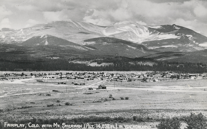 Photographic postcard with Mount Sherman and a Depot